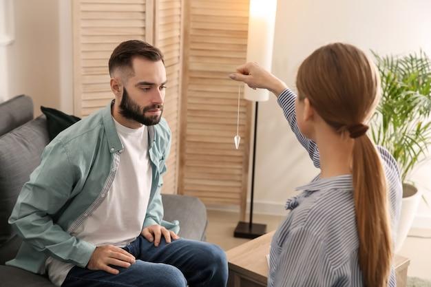 Młody mężczyzna podczas sesji hipnozy w gabinecie psychologa