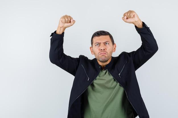 Młody mężczyzna podnosi zaciśnięte pięści w koszulce, kurtce i wygląda na zdenerwowanego. przedni widok.