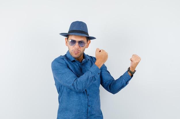 Młody mężczyzna podnosi zaciśnięte pięści w niebieskiej koszuli, kapeluszu i wygląda fajnie. przedni widok.