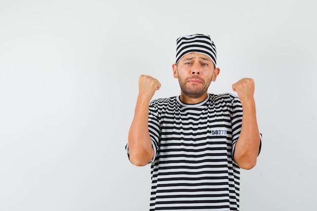 Młody mężczyzna podnosi zaciśnięte pięści w pasiastej koszulce, kapeluszu i wygląda na zdenerwowanego.