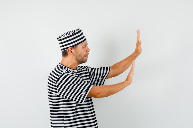 Młody mężczyzna, podnosząc ręce w sposób zapobiegawczy w t-shirt w paski, kapelusz i wyglądający na zirytowanego.