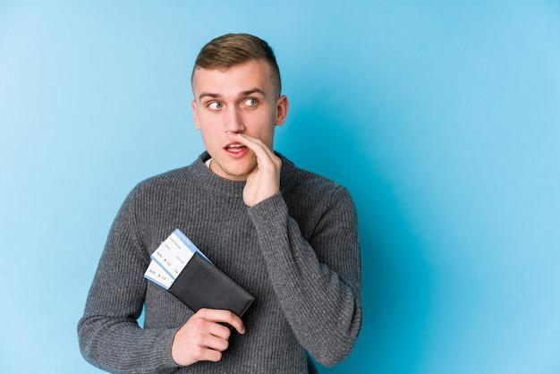 Młody mężczyzna podróżnik posiadający kartę pokładową mówi sekretną wiadomość o hamowaniu na gorąco i patrzy na bok