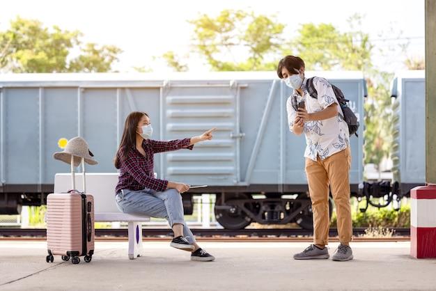 Młody mężczyzna podróżny plecak z maską i telefonem w ręku, prosząc o pomoc kobietę siedzącą i wskazującą na schodach w metrze, odległość covid
