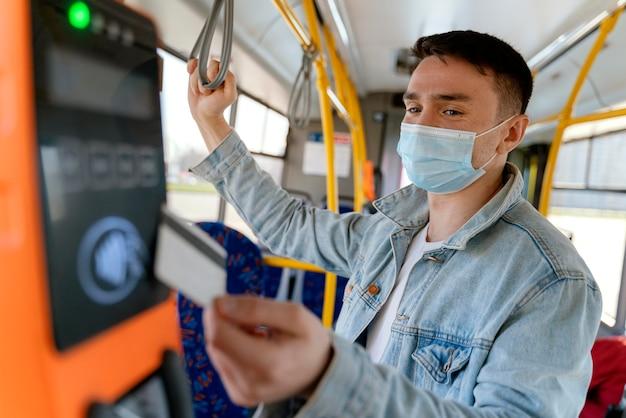 Młody mężczyzna podróżujący autobusem miejskim płacący kartą autobusową