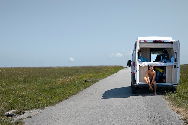 Młody mężczyzna podróżujący samotnie vanem