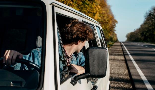 Młody mężczyzna podróżujący swoją furgonetką