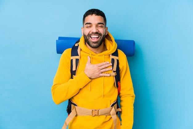 Młody mężczyzna podróżujący z plecakiem arabian śmieje się głośno, trzymając rękę na piersi.