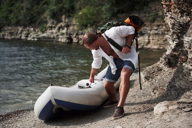 Młody mężczyzna podróżuje z plecakiem za pomocą łodzi. sposób życia w podróży i przyroda z przyrodą