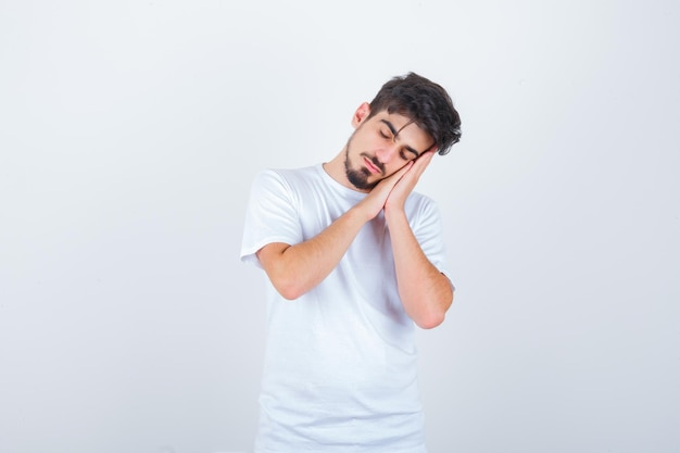 Młody mężczyzna poduszkuje twarz na dłoniach w koszulce i wygląda na zaspanego