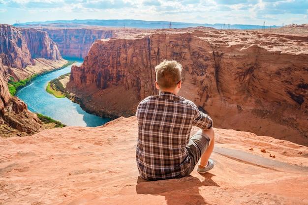 Młody mężczyzna podziwia niesamowity widok na tamę glen canyon i rzekę kolorado w page arizona