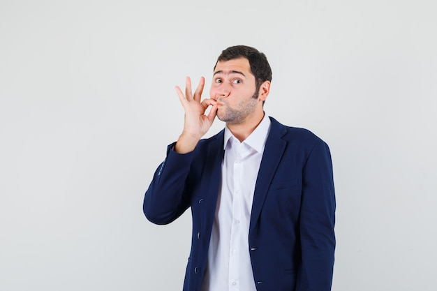 Młody mężczyzna pokazano gest zip w koszuli