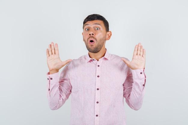 Młody mężczyzna pokazując gest odmowy w różowej koszuli i patrząc przestraszony, widok z przodu.