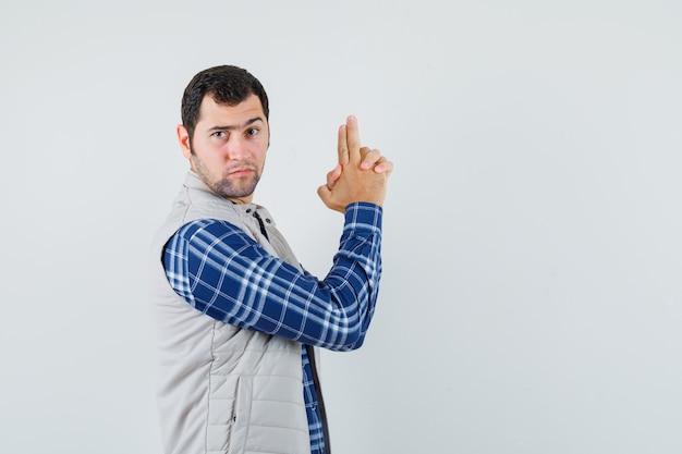 Młody mężczyzna pokazując gest pistoletu w koszuli, kurtce bez rękawów i patrząc uważnie.