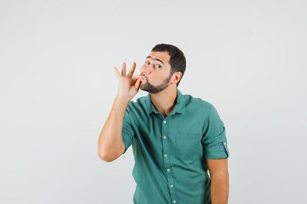 Młody mężczyzna pokazując gest zip w zielonej koszuli i patrząc skupiony. przedni widok.