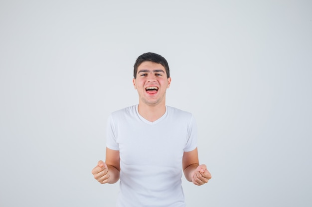 Młody mężczyzna pokazując gest zwycięzcy w koszulce i patrząc na szczęście. przedni widok.