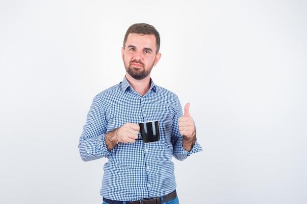 Młody mężczyzna pokazując kciuk do góry trzymając kubek w koszuli, dżinsach i patrząc zachwycony, widok z przodu.