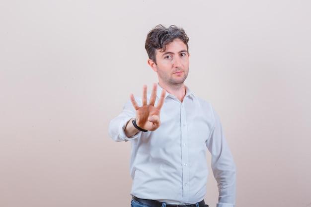Młody mężczyzna pokazujący cztery palce w białej koszuli, dżinsach i wyglądający pewnie