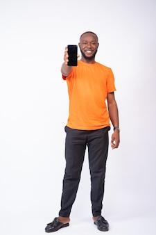 Młody mężczyzna pokazujący ekran telefonu na białym tle