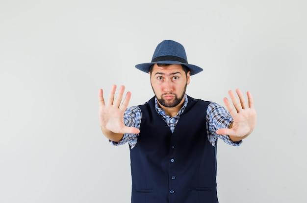 Młody mężczyzna pokazujący gest odmowy w koszuli, kamizelce, kapeluszu i wyglądający na przestraszonego.