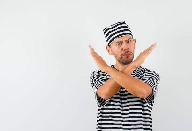 Młody mężczyzna pokazujący gest odmowy w t-shirt w paski, kapelusz i wyglądający na zirytowanego.