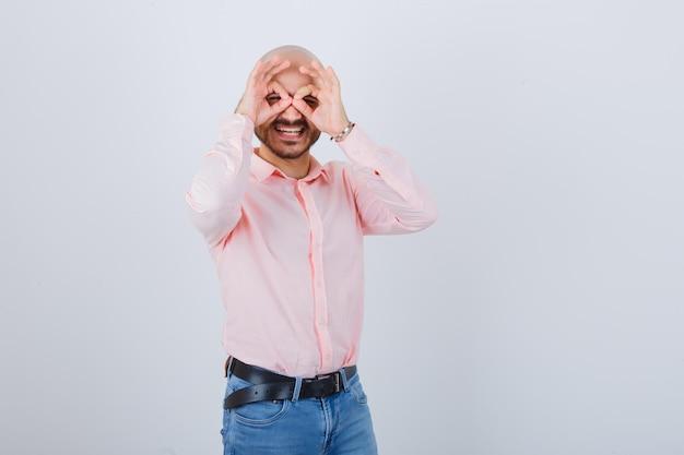 Młody mężczyzna pokazujący gest okularów
