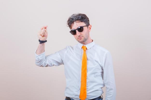Młody mężczyzna pokazujący gest pieniędzy w koszuli, krawacie