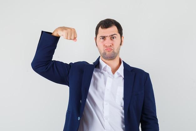 Młody mężczyzna pokazujący mięśnie ramienia w koszuli, kurtce i wyglądający złośliwie