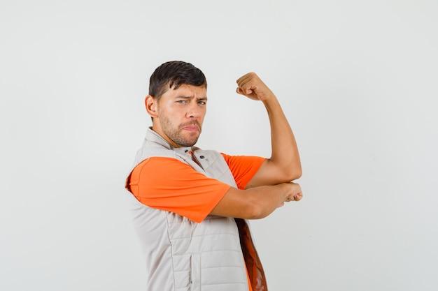 Młody mężczyzna pokazujący mięśnie ramion w koszulce, kurtce i wyglądający na potężnego. przedni widok.