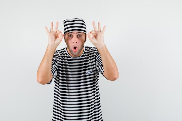 Młody mężczyzna pokazujący ok gest w t-shirt, kapelusz i wyglądający na zdumiony, widok z przodu.