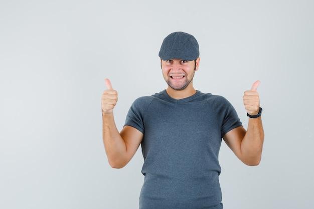 Młody mężczyzna pokazujący podwójne kciuki do góry w szarej czapce t-shirtu i wyglądający radośnie