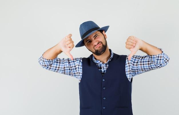 Młody mężczyzna pokazujący podwójne kciuki w dół w koszuli, kamizelce, kapeluszu i niezadowolony.