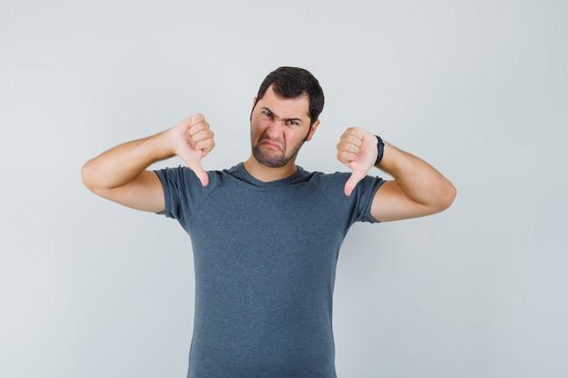 Młody mężczyzna pokazujący podwójne kciuki w dół w szarym t-shircie i wyglądający na przygnębionego. przedni widok.