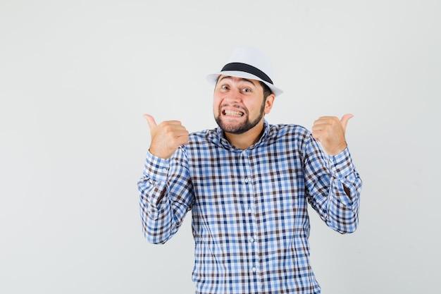 Młody mężczyzna pokazujący podwójne kciuki w kraciastej koszuli, kapeluszu i wyglądający wesoło, widok z przodu.