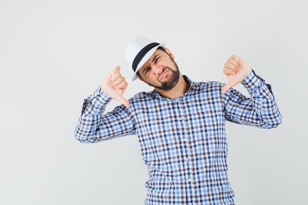 Młody mężczyzna pokazujący podwójny kciuk w dół w kraciastej koszuli, kapeluszu i wyglądający na niezadowolonego. przedni widok.