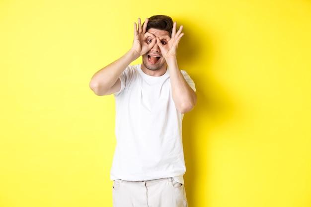Młody mężczyzna pokazujący śmieszne twarze i trzymający język, stojący zabawnie na żółtym tle