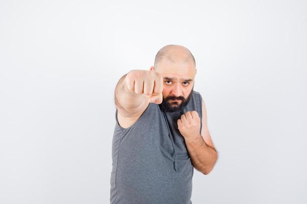 Młody mężczyzna pokazujący zaciśnięte pięści w bluzie bez rękawów i wyglądający złośliwie, widok z przodu.