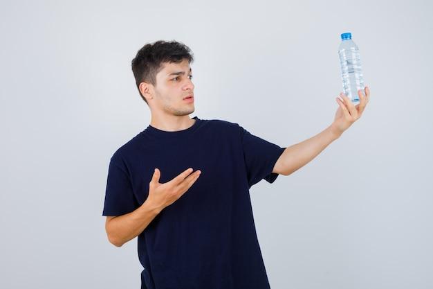 Młody mężczyzna pokazuje butelkę wody w czarnej koszulce i wygląda zdziwiony. przedni widok.