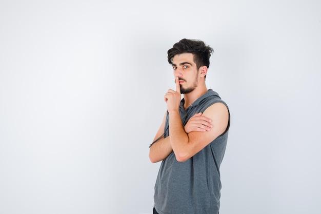 Młody mężczyzna pokazuje gest ciszy w szarej koszulce i wygląda poważnie