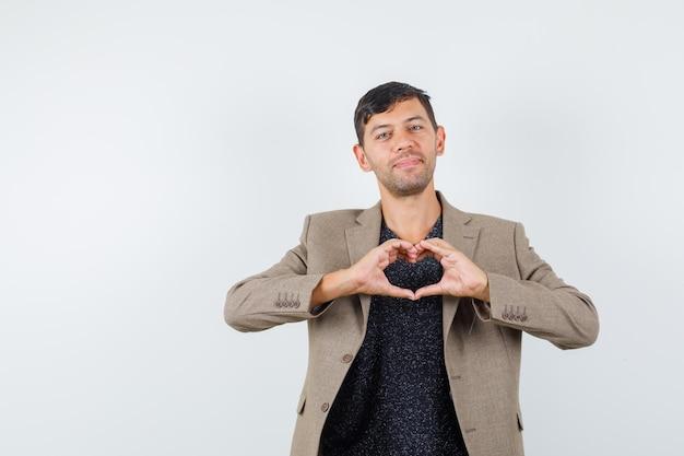 Młody mężczyzna pokazuje gest miłości w szarawo brązową kurtkę, czarną koszulę i wyglądający sympatycznie, widok z przodu. miejsce na tekst