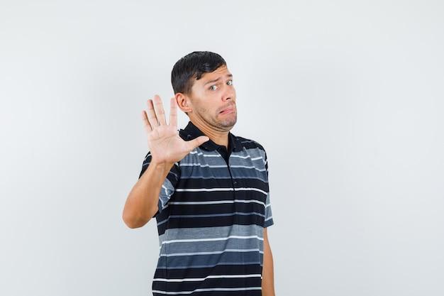 Młody mężczyzna pokazuje gest odmowy w t-shirt i przestraszony. przedni widok.