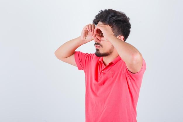 Młody mężczyzna pokazuje gest okulary w t-shirt i wygląda śmiesznie, widok z przodu.