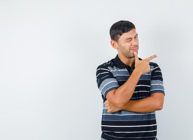 Młody mężczyzna pokazuje gest pistoletu i mrugając okiem w koszulce, widok z przodu.