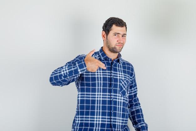 Młody mężczyzna pokazuje gest pistoletu w kraciastej koszuli i wygląda pewnie.