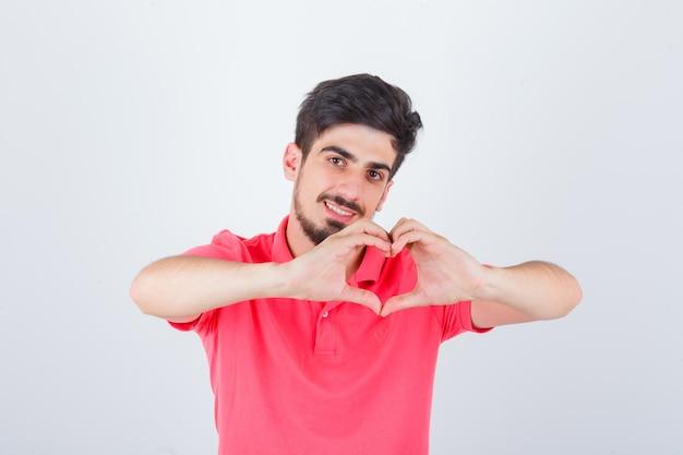 Młody mężczyzna pokazuje gest serca w różowym t-shirt i wygląda pewnie. przedni widok.