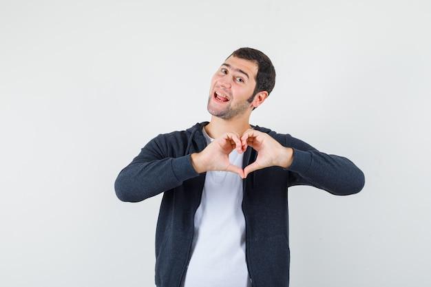 Młody mężczyzna pokazuje gest serca w t-shirt, kurtce i patrząc wesoło. przedni widok.