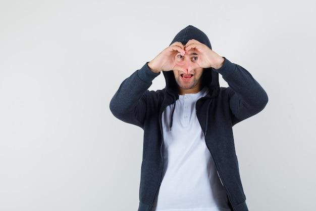 Młody mężczyzna pokazuje gest serca w t-shirt, kurtkę i patrząc pewnie, z przodu.