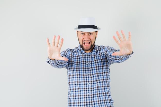 Młody mężczyzna pokazuje gest stopu, krzycząc w kraciastej koszuli, kapeluszu i wyglądając na wzburzonego. przedni widok.