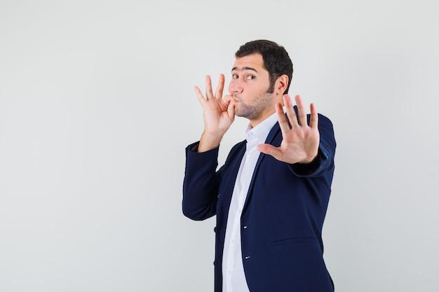 Młody mężczyzna pokazuje gest stopu z zamkniętymi ustami jako zamek błyskawiczny w koszuli
