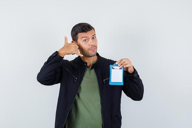 Młody mężczyzna pokazuje gest telefonu trzymając schowek w koszulce, kurtce i patrząc pomocny, widok z przodu.
