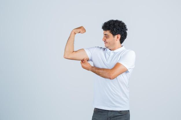 Młody mężczyzna pokazuje gest władzy, patrząc na to w białej koszulce i dżinsach i wygląda na szczęśliwego. przedni widok.